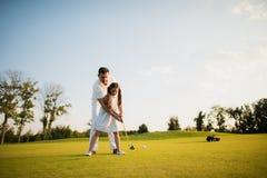 Första slag En man undervisar hans dotter att spela golf och flickan med hans hjälp som göras den första golfklubben royaltyfri foto