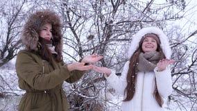 Första snö, unga kvinnor som tycker om vinterdag och låssnöflingor med händer upp i, parkerar lager videofilmer