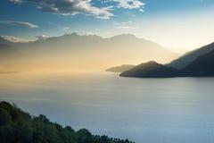 Första solstrålar över sjön Como som ser från Italien in i Schweiz royaltyfria bilder