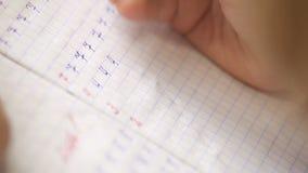 Första steg skriftligen: den lilla eleven skriver siffror i fyrkantig rasteranteckningsbok lager videofilmer