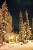 Första tecken av nordliga ljus ovanför den sörjaträden och kabinen Royaltyfri Fotografi