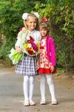 Första väghyvel för stående och hennes mer unga syster på väg till skolan royaltyfri fotografi