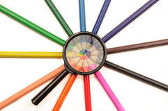 Förstoringsapparat och färgade blyertspennor Arkivbilder