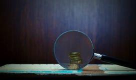Förstoringsapparat och guld- mynt Arkivfoton