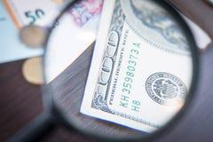 Förstoringsapparaten fokuserade på den 100 dollar sedeln, euroet, dollaren, reminbisedlar Royaltyfri Bild