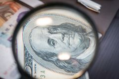 Förstoringsapparaten fokuserade på den 100 dollar sedeln, euroet, dollaren, reminbisedlar Arkivbilder