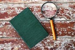 Förstoringsglas eller loupe med boken Royaltyfria Bilder