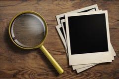 Förstoringsglas eller loupe med gamla fotoramar Fotografering för Bildbyråer