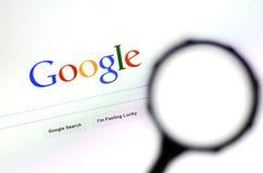 Förstoringsglas mot Google homepage Royaltyfri Foto