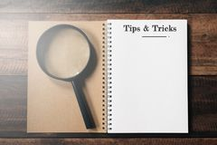 Förstoringsglas och anteckningsbok med SPETS- OCH TRICKord med kopieringsutrymme på trätabellen arkivbild