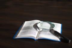 Förstoringsglas och bok Arkivfoto