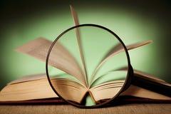 Förstoringsglas och en bok Royaltyfri Bild