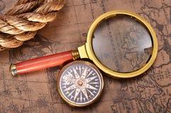 Förstoringsglas och kompass på den forntida översikten Arkivbild