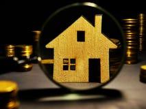 Förstoringsglas och modell av huset Egenskapsinvesteringbedömning arkivbild