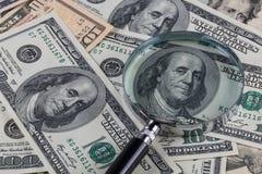 Förstoringsglas och pengar Arkivfoton