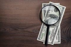 Förstoringsglas och pengar på träbakgrund Fotografering för Bildbyråer