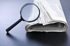 Förstoringsglas och tidning Arkivbild