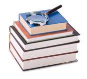 Förstoringsglas på böcker royaltyfria bilder