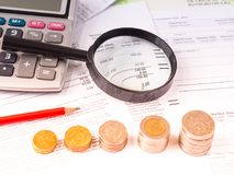 Förstoringsglas på bokföringsunderlag med räknemaskinen och bunten av mynt Arkivfoton
