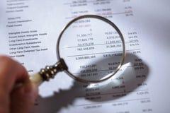 Förstoringsglas på finansiell rapport arkivfoto