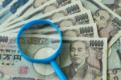 Förstoringsglas på högen av Japan yensedlar som finansiell eller royaltyfria foton