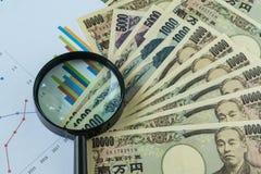 Förstoringsglas på högen av sedlar för japansk yen med utskrivavet Arkivbild