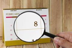 Förstoringsglaset i hand på kalender kan du se åttonde dag Royaltyfria Bilder