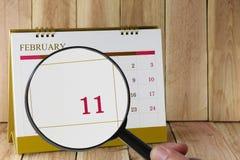 Förstoringsglaset i hand på kalender kan du se dag elva av Fotografering för Bildbyråer