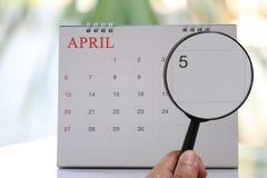 Förstoringsglaset i hand på kalender kan du se dag fem av mo Royaltyfria Bilder