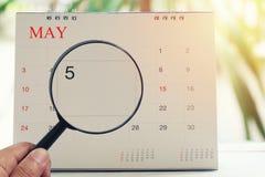Förstoringsglaset i hand på kalender kan du se dag fem av mo Arkivfoton