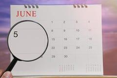 Förstoringsglaset i hand på kalender kan du se dag fem av mo Royaltyfri Foto