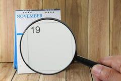 Förstoringsglaset i hand på kalender kan du se dag nio av mo Royaltyfri Fotografi