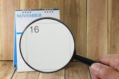 Förstoringsglaset i hand på kalender kan du se dag sexton av Arkivbild