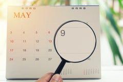 Förstoringsglaset i hand på kalender kan du se den nionde dagen av M Arkivfoto
