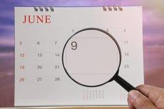 Förstoringsglaset i hand på kalender kan du se den nionde dagen av M Royaltyfria Bilder