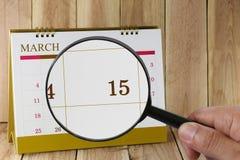 Förstoringsglaset i hand på kalender kan du se femtonde dag Fotografering för Bildbyråer