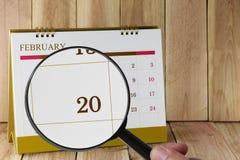 Förstoringsglaset i hand på kalender kan du se tjugonde dag Arkivbilder