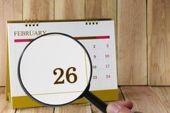 Förstoringsglaset i hand på kalender kan du se tjugosex dag Arkivbild