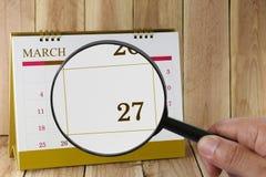 Förstoringsglaset i hand på kalender kan du se tjugosju D Arkivbilder