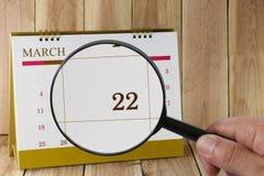 Förstoringsglaset i hand på kalender kan du se tjugotvå dag Arkivfoton