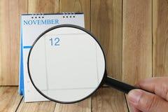 Förstoringsglaset i hand på kalender kan du se tolfte dag av Arkivfoton