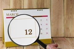 Förstoringsglaset i hand på kalender kan du se tolfte dag av Royaltyfria Foton