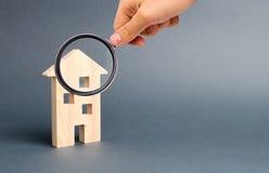 Förstoringsglaset ser envåning som bygger det bostads- huset på en grå bakgrund Inteckna och kreditera arkivbild