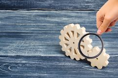 Förstoringsglaset ser kugghjulen av träställningen på en mörk träbakgrund Begrepp av teknologi och bransch arkivfoton