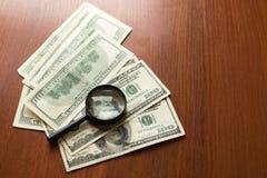 Förstoringsglaslögner på amerikanska dollar på träbakgrund arkivfoto