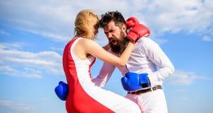 Försvara din åsikt i konfrontation Mannen och kvinnan slåss bakgrund för himmel för boxninghandskar Attack är bästa försvar kvinn arkivfoto