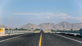 Försvinna punkt på vägen med berg i bakgrunden Arkivfoton