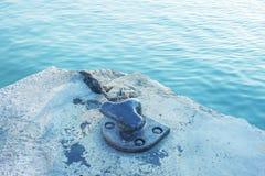 Förtöja repet och pollaren på bakgrund för havsvatten Royaltyfri Bild