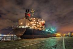 Förtöjd oljetanker på natten med en dramatisk molnig himmel, port av Antwerp, Belgien fotografering för bildbyråer