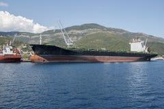 Förtöjd tankfartyg nära kusten mot bakgrunden av den gröna monteringen Royaltyfria Bilder